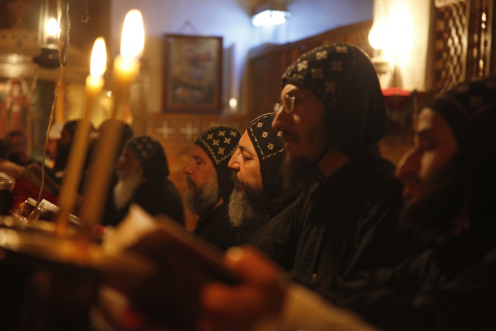 FILE - In this April 17, 2013 photo, monks pray at the ancient monastery of St. Anthony in the eastern desert southeast of Cairo, Egypt. The killing o...