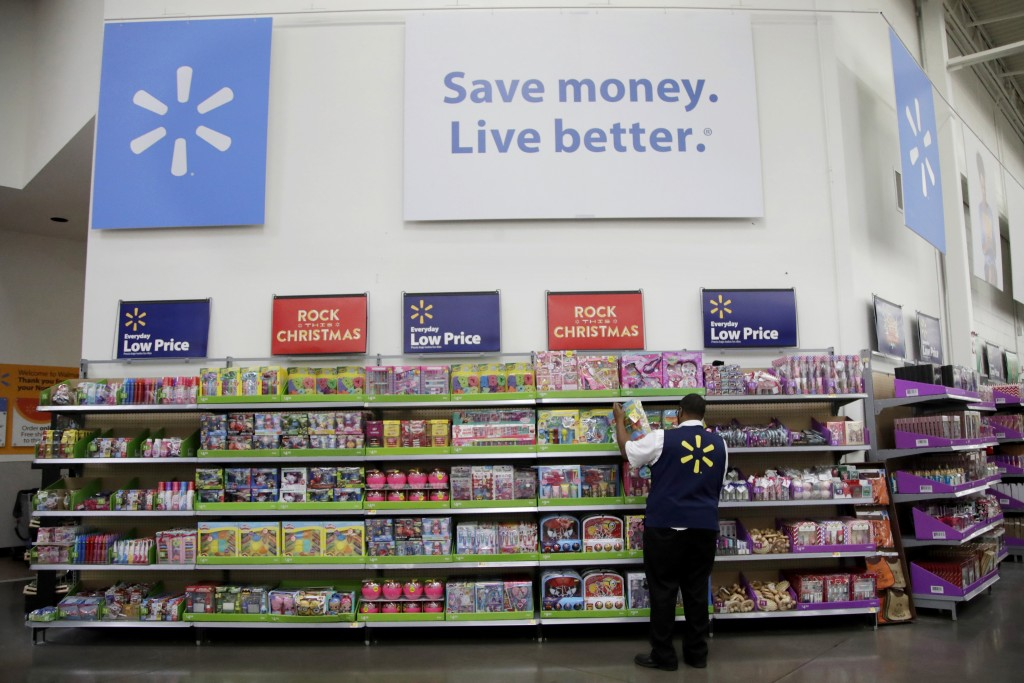 FILE- In this Nov. 9, 2017, file photo, a Walmart employee scans items while conducting an exercise during a Walmart Academy class session at the stor...