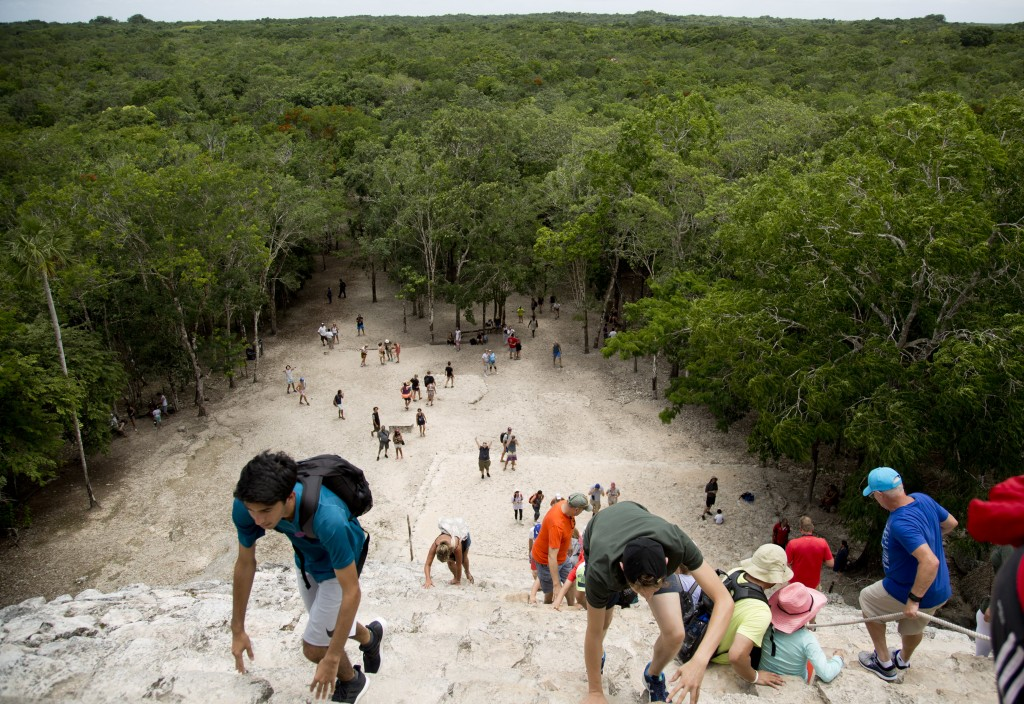 In this Aug. 1, 2018 photo, tourists climb a temple at the archeological site of Coba, in Mexico's Yucatan Peninsula. Mexico's president-elect Andres ...