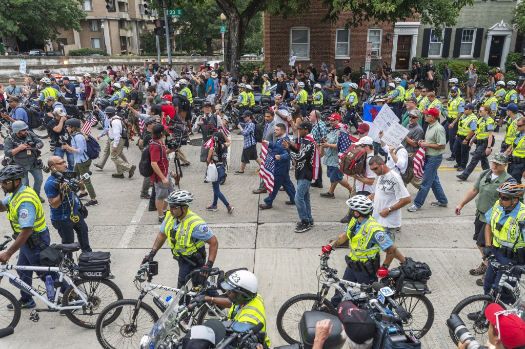 """White nationalists, led by Jason Kessler, center, wearing a suit and carrying a flag, march to Lafayette Square during the """"Unite the Right 2"""" rally i..."""