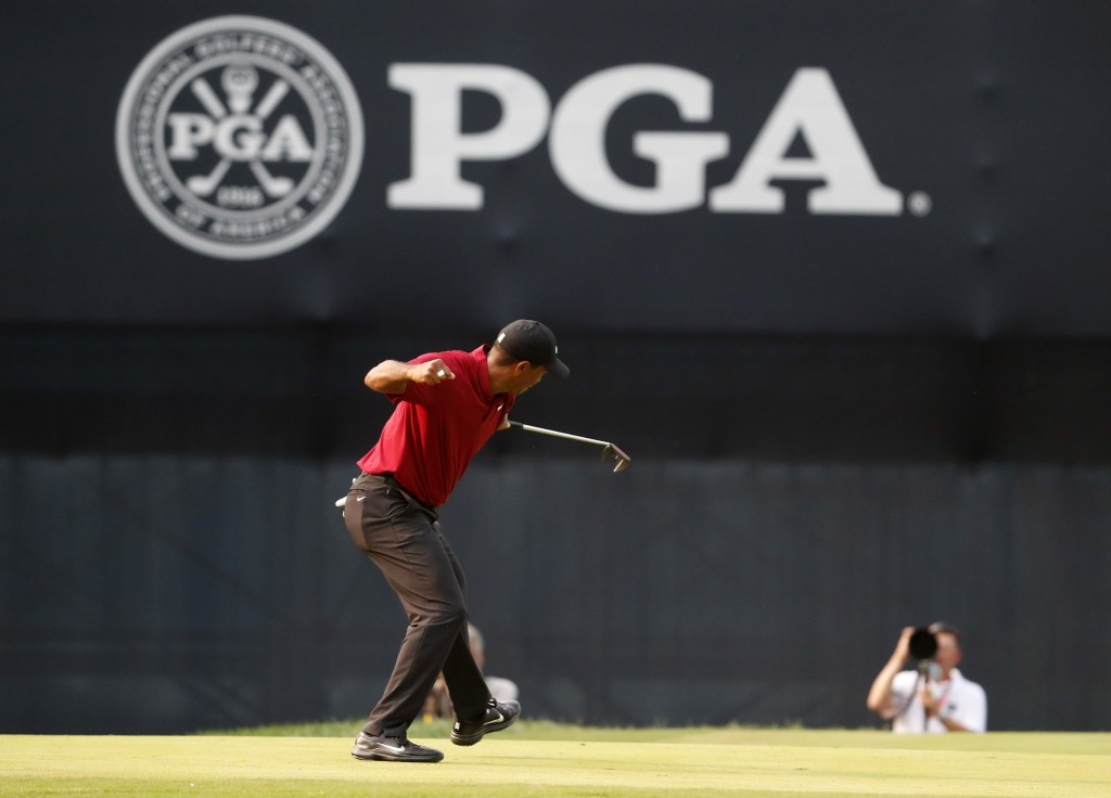 Tiger Woods celebrates his birdie putt on the 18th green during the final round of the PGA Championship golf tournament at Bellerive Country Club, Sun...