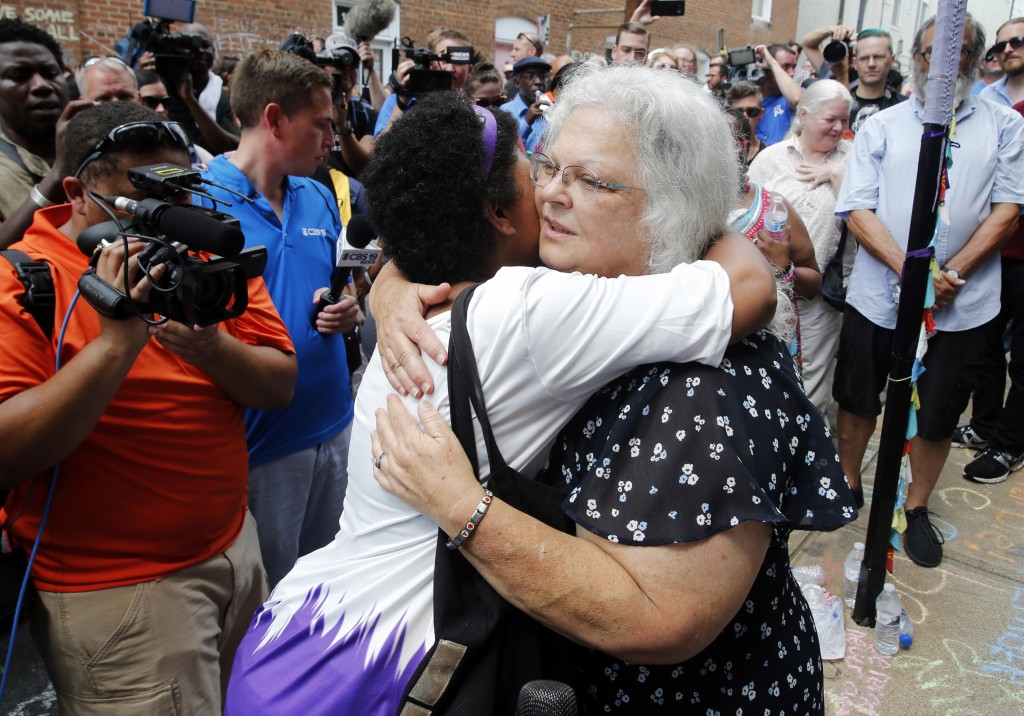 Susan Bro, mother of Heather Heyer who was killed during last year's Unite the Right rally, embraces supporters after laying flowers at the spot her d...