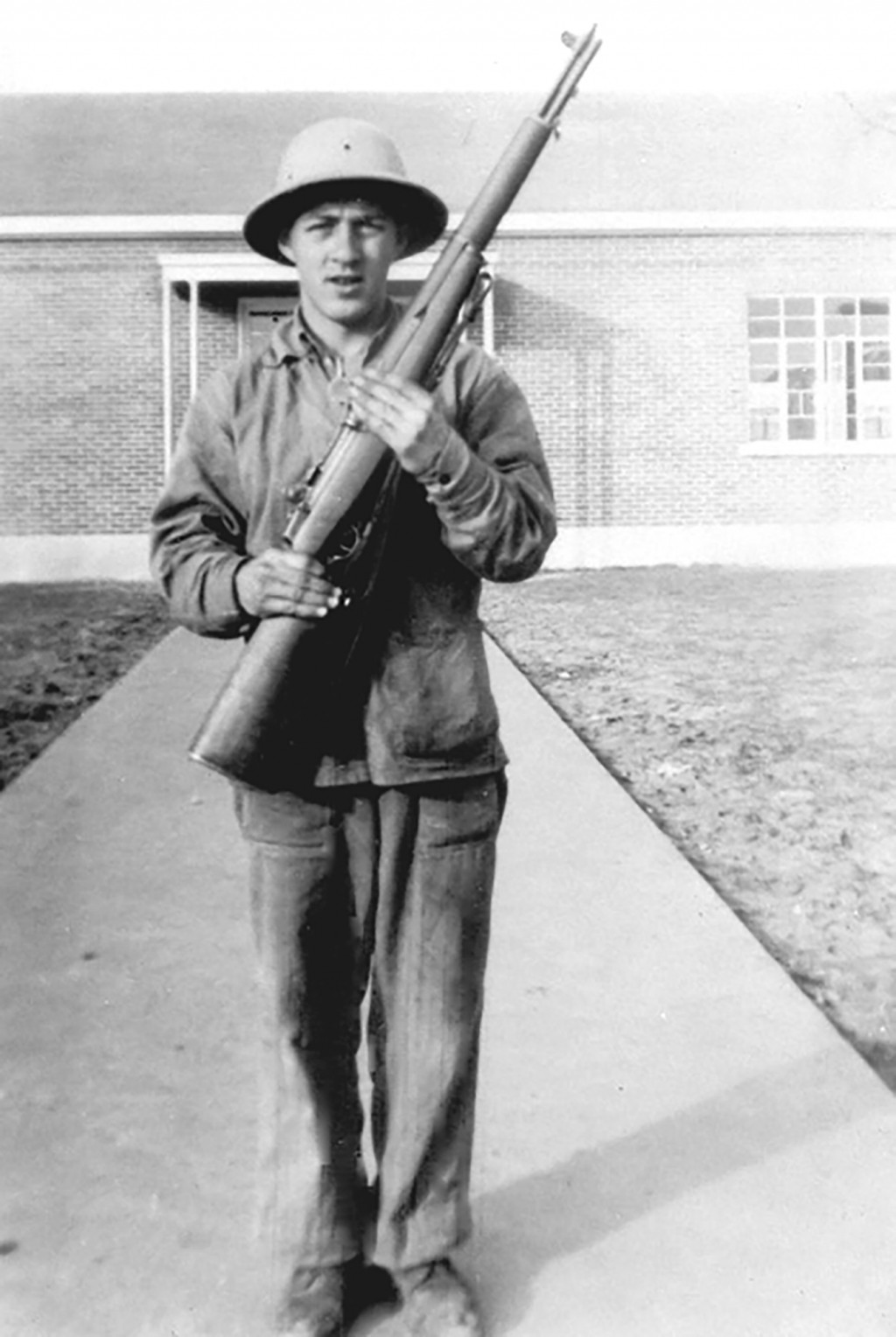 In this early 1940s photo provided by the United States Marine Corps, Emil Ragucci poses with a rifle. Decades after his death in the World War II Bat...