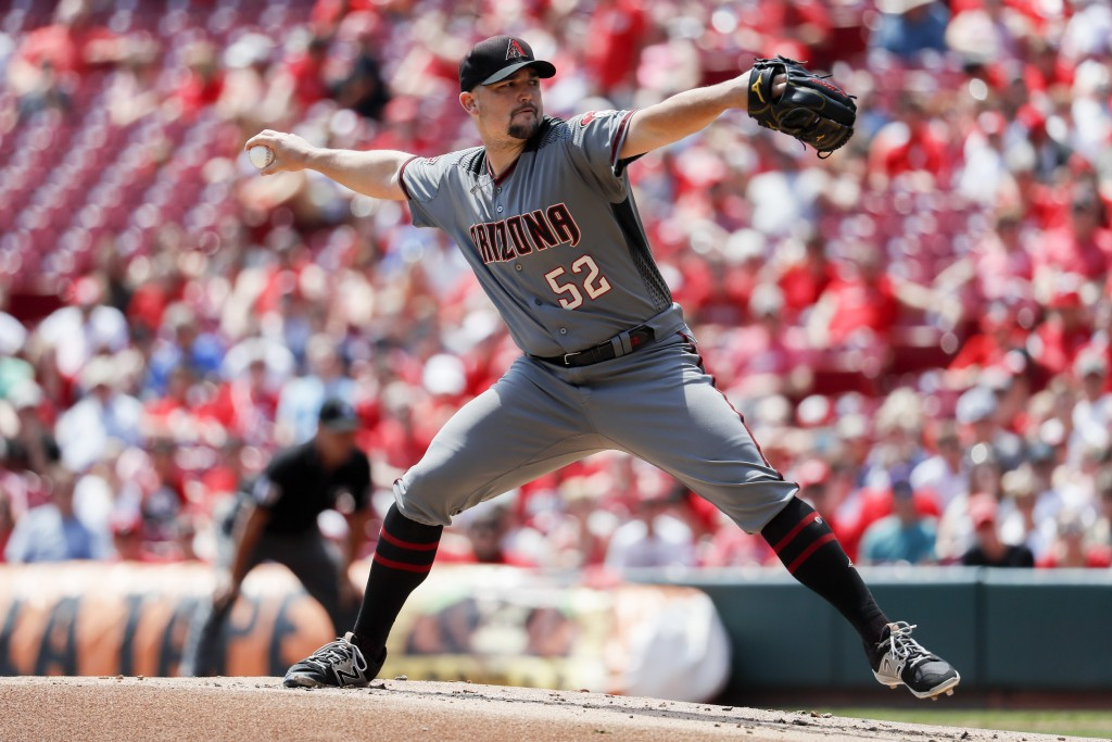 Arizona Diamondbacks starting pitcher Zack Godley throws in the first inning of a baseball game against the Cincinnati Reds, Sunday, Aug. 12, 2018, in