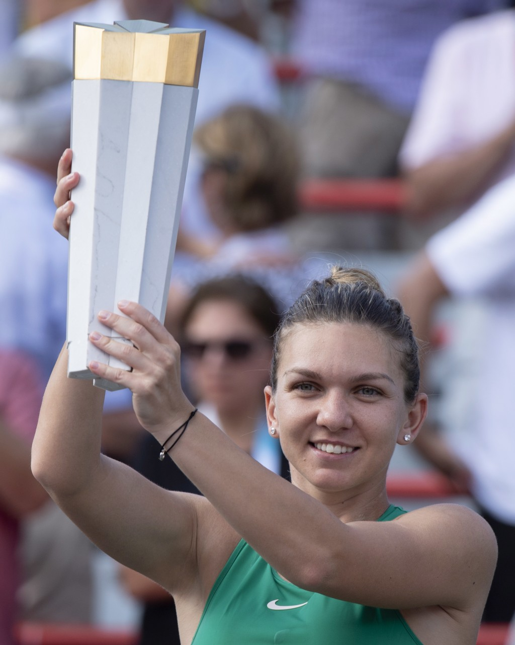 Simona Halep, of Romania, holds the trophy after defeating Sloane Stephens, of the United States, in the final of the Rogers Cup women's tennis tourna