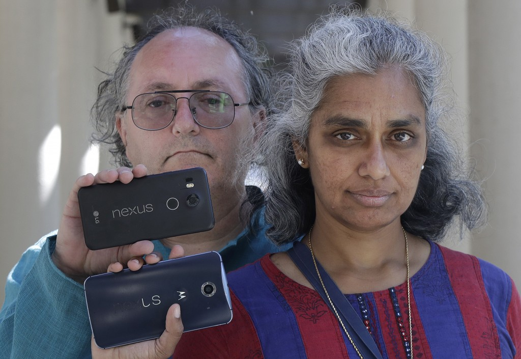 In this July 25, 2018 photo, Kalyanaraman Shankari, right, and her husband Thomas Raffill hold their phones while posing for photos in Mountain View, ...