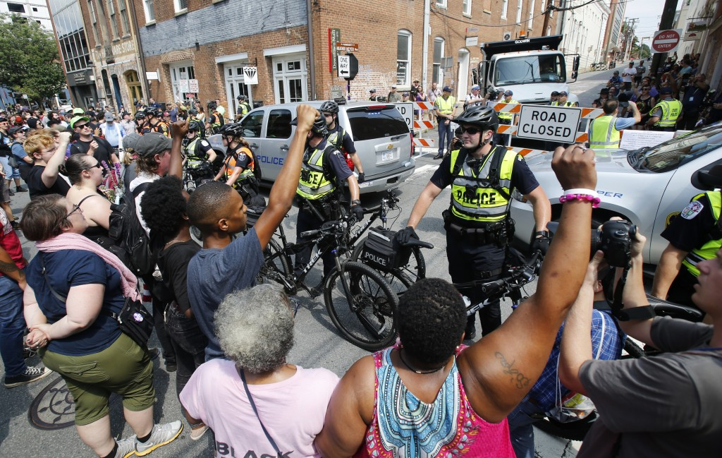 Demonstrators confront police at the intersection where Heather Heyer was killed last year as they mark the anniversary of the Unite the Right rally i...