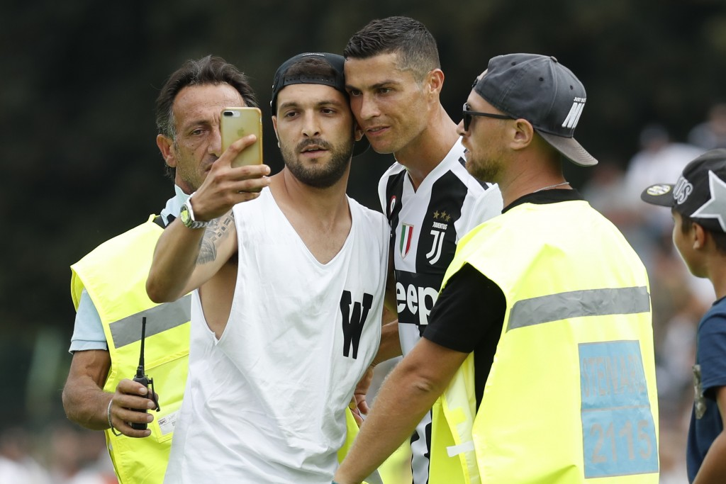 A fan takes a selfie photo with Cristiano Ronaldo during a friendly match between the Juventus A and B teams, in Villar Perosa, northern Italy, Sunday