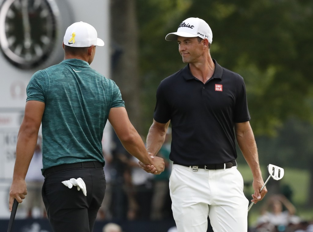 Brooks Koepka, left, is congratulated by playing partner Adam Scott after Koepka won the PGA Championship golf tournament at Bellerive Country Club, S...