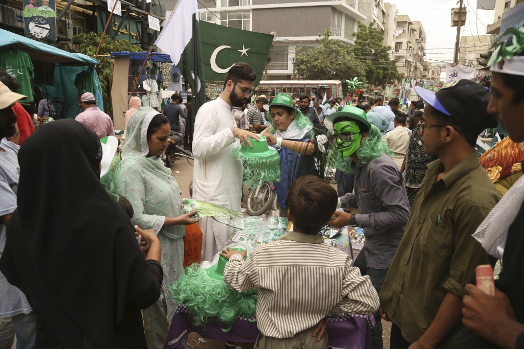 People buy national flags, badges and related merchandise to celebrate the 71st Independence Day, in Karachi, Pakistan, Monday, Aug. 13, 2018. Pakista...