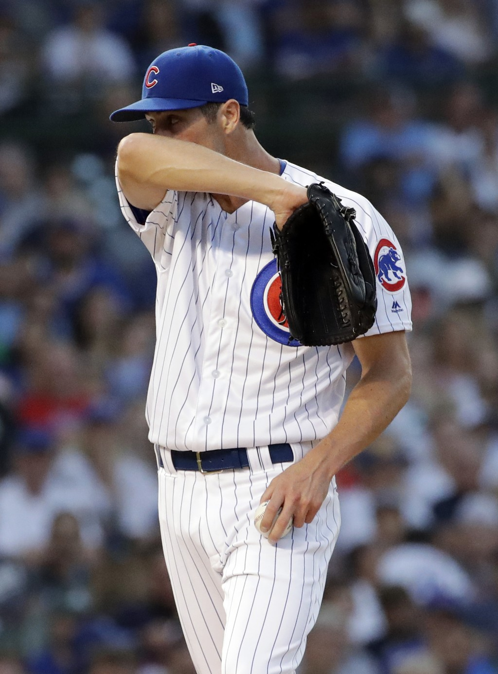Chicago Cubs starting pitcher Cole Hamels wipes his face during the second inning of a baseball game against the Washington Nationals, Sunday, Aug. 12...