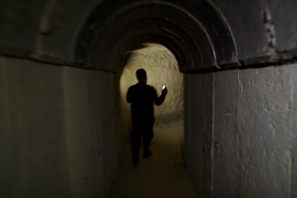 In this July 15, 2018 photo, a Syrian official walks in a tunnel leading to underground cells in the abandoned Tawbeh Prison, where over the years the...