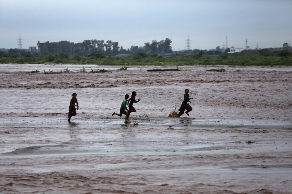 Indian children play in the River Tawi flooded following monsoon rains in Jammu, India, Monday, Aug.13, 2018. India's monsoon season runs from June to...