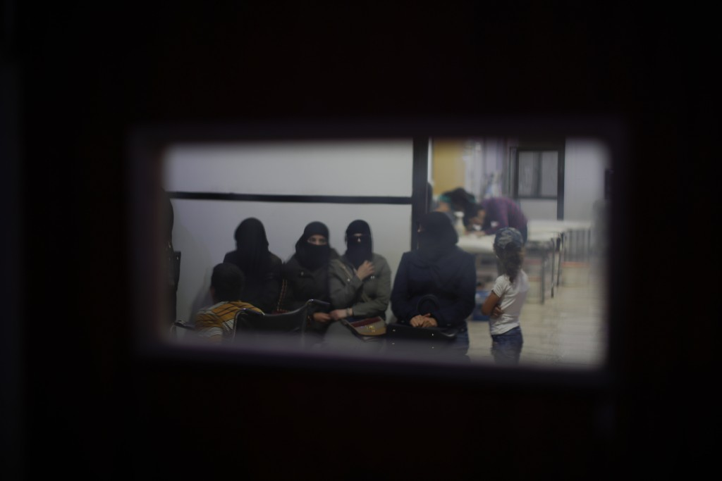 In this July 15, 2018 photo, Syrian women wait in an underground hospital that insurgents referred to as Point One, in Douma, near the Syrian capital ...