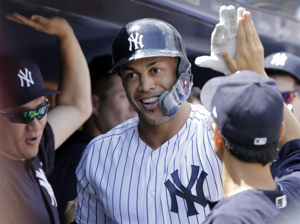 New York Yankees' Giancarlo Stanton is greeted in the dugout after hitting a solo home run during the first inning of a baseball game against the Texa