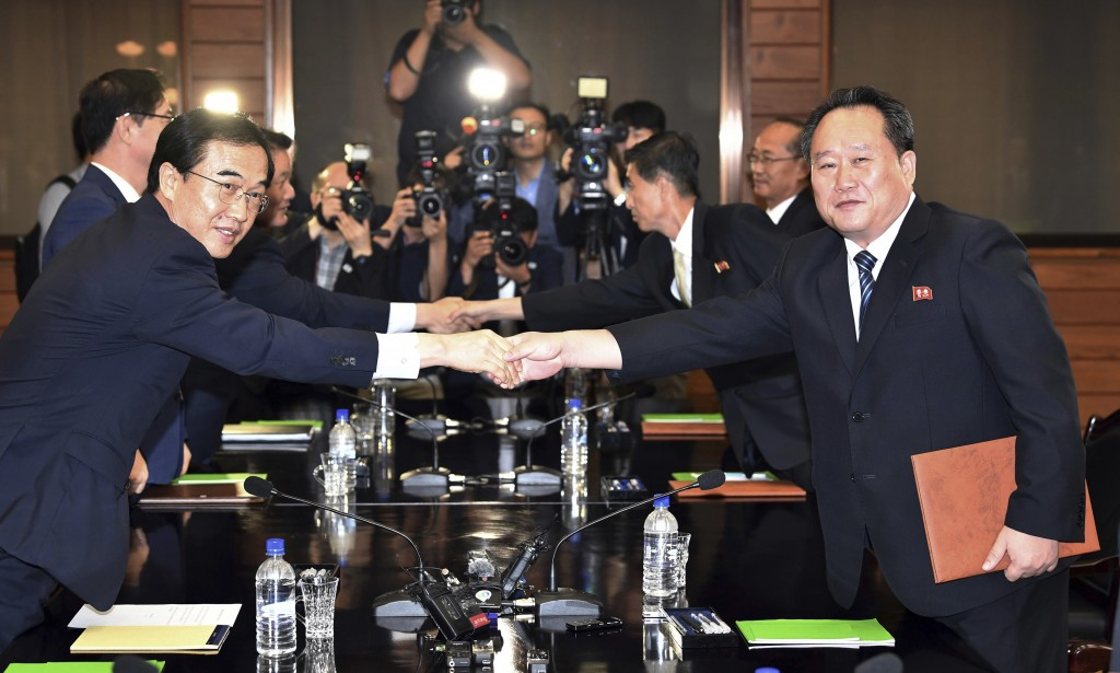 South Korean Unification Minister Cho Myoung-gyon, left, shakes hands with his North Korean counterpart Ri Son Gwon after their meeting at the norther...