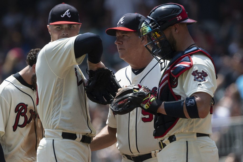 Atlanta Braves starting pitcher Sean Newcomb, left, is visited at the mound by pitching coach Chuck Hernandez and catcher Tyler Flowers, right, after