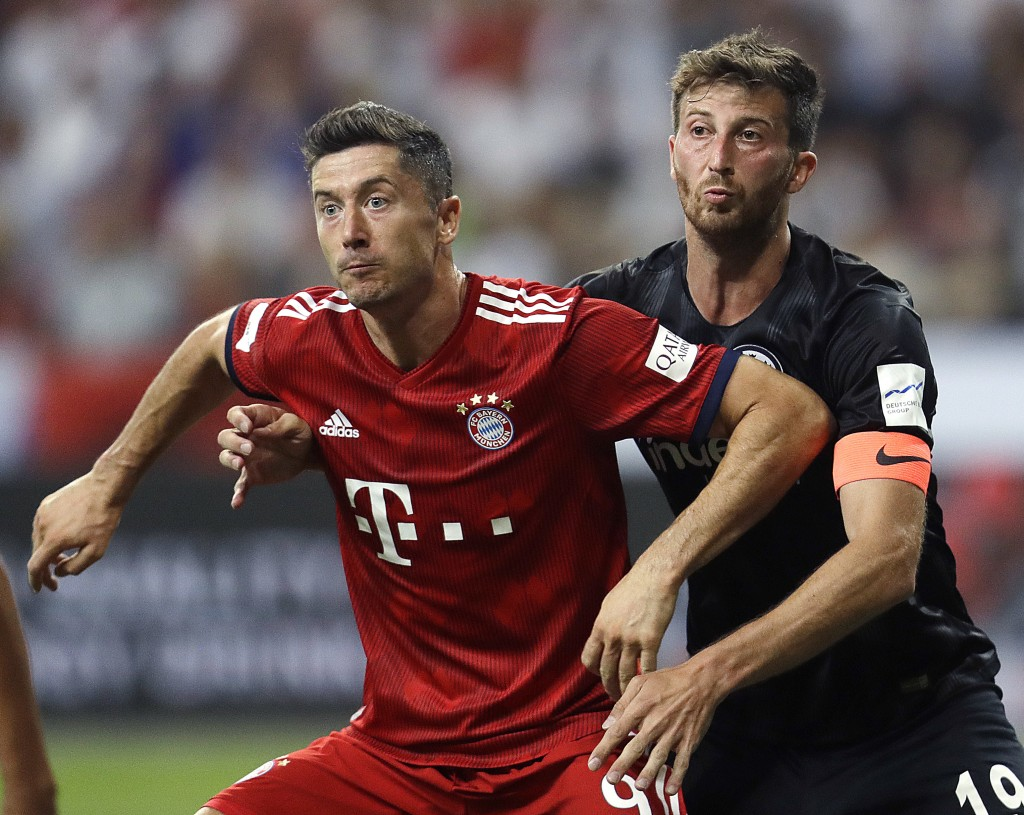 Munich's Robert Lewandowski, left, and Frankfurt's David Abraham struggle during a soccer Supercup match between Eintracht Frankfurt and Bayern Munich