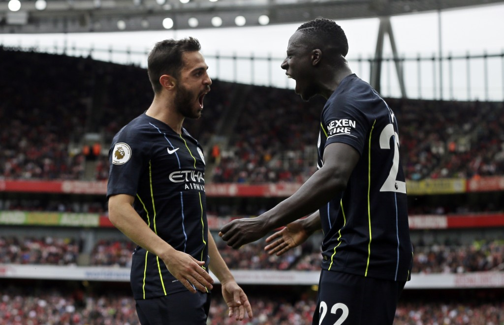 Manchester City's Bernardo Silva celebrates with teammate Benjamin Mendy, right, after scoring his side's second goal during the English Premier Leagu...