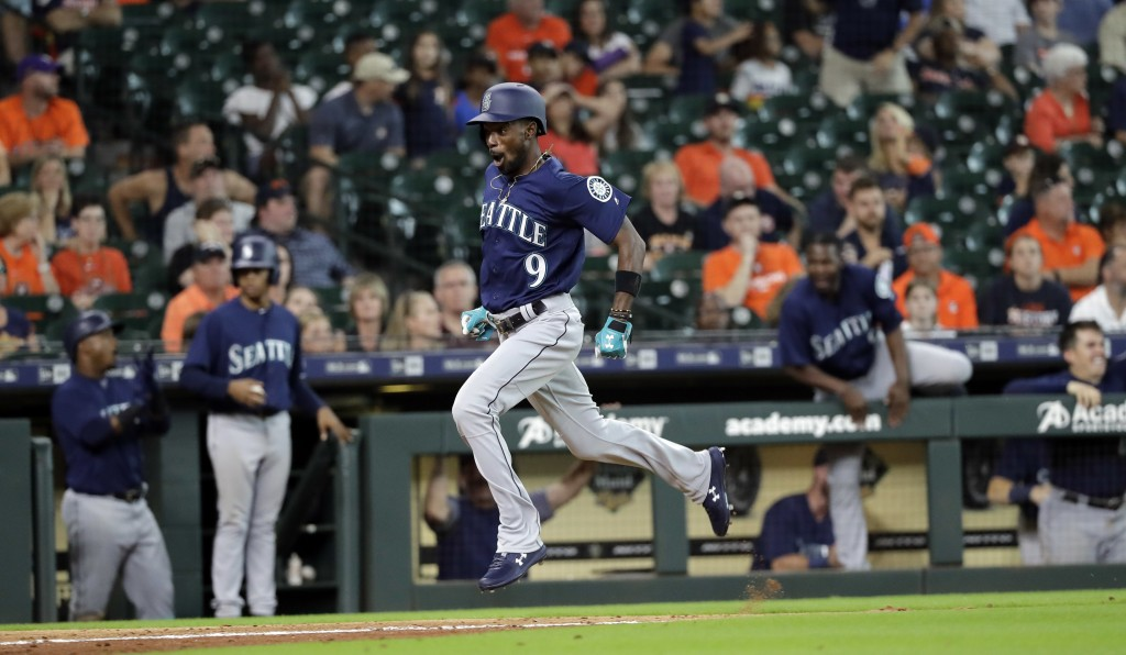 Seattle Mariners' Dee Gordon (9) scores a run during the 10th inning of a baseball game against the Houston Astros Sunday, Aug. 12, 2018, in Houston.