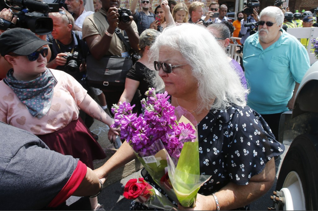 Susan Bro, center, mother of Heather Heyer who was killed during last year's Unite the Right rally, and her husband, Kim, right, speak to supporters a...