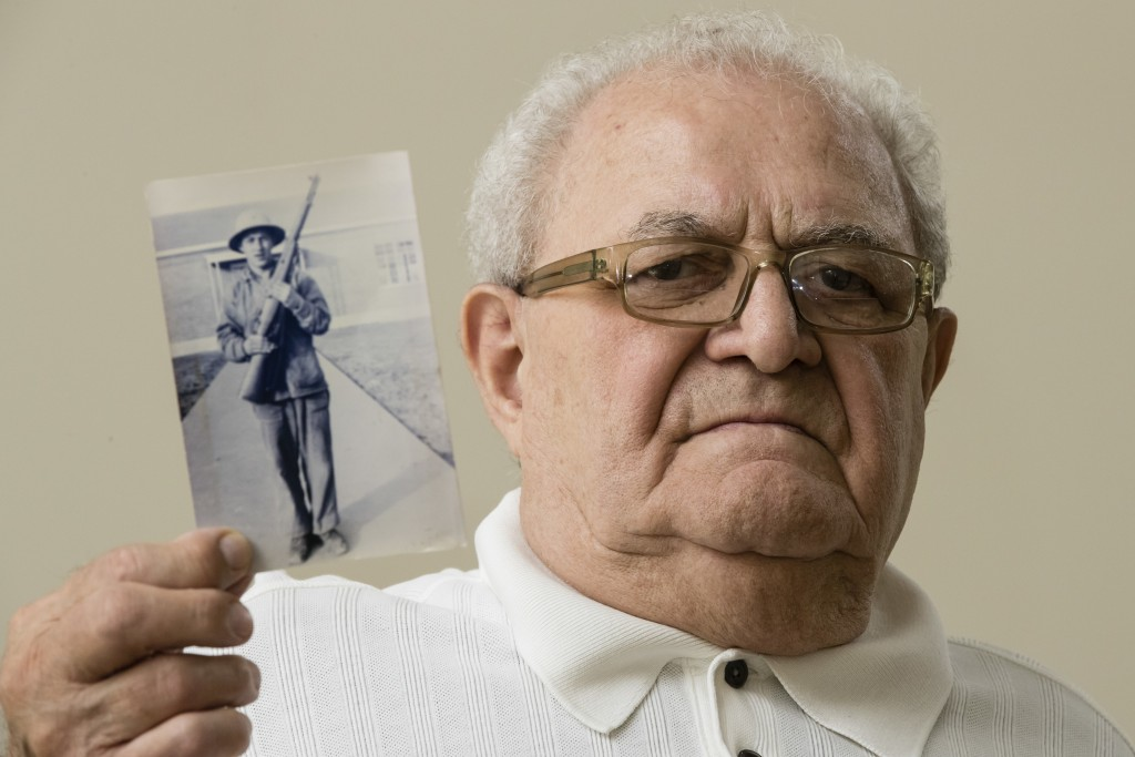 In this July 31, 2018 photo, Dominic Ragucci poses for a portrait in Philadelphia with a photo of his brother, Emil, who was killed in action during W...