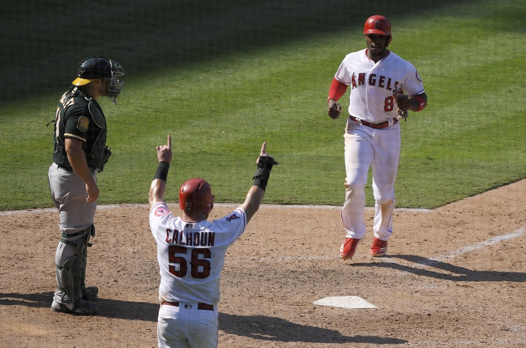 Los Angeles Angels' Justin Upton, right, scores on a single by Shohei Ohtani, of Japan, as Kole Calhoun, center, celebrates and Los Angeles Angels thi