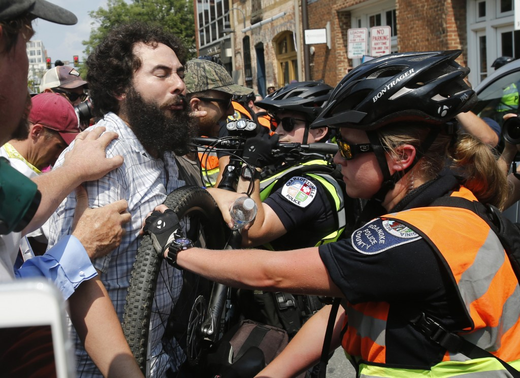 A demonstrator confronts police at the intersection where Heather Heyer was killed last year as they mark the anniversary of the Unite the Right rally...