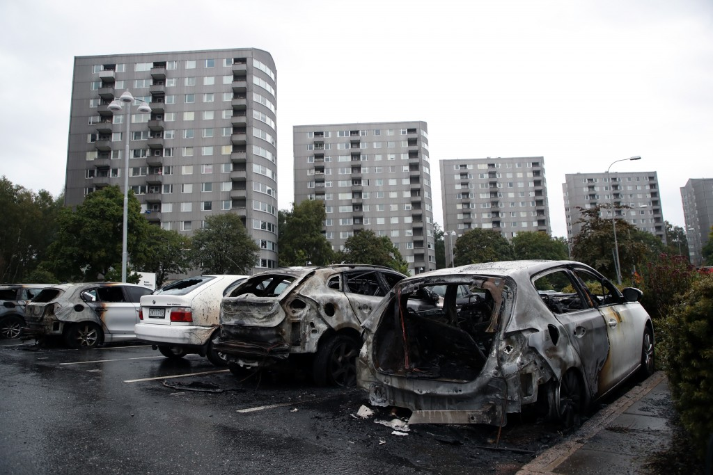 Burned cars parked at Frolunda Square in Gothenburg, Tuesday,  Aug. 14, 2018. Masked youth torched dozens of cars overnight in Sweden and threw rocks ...