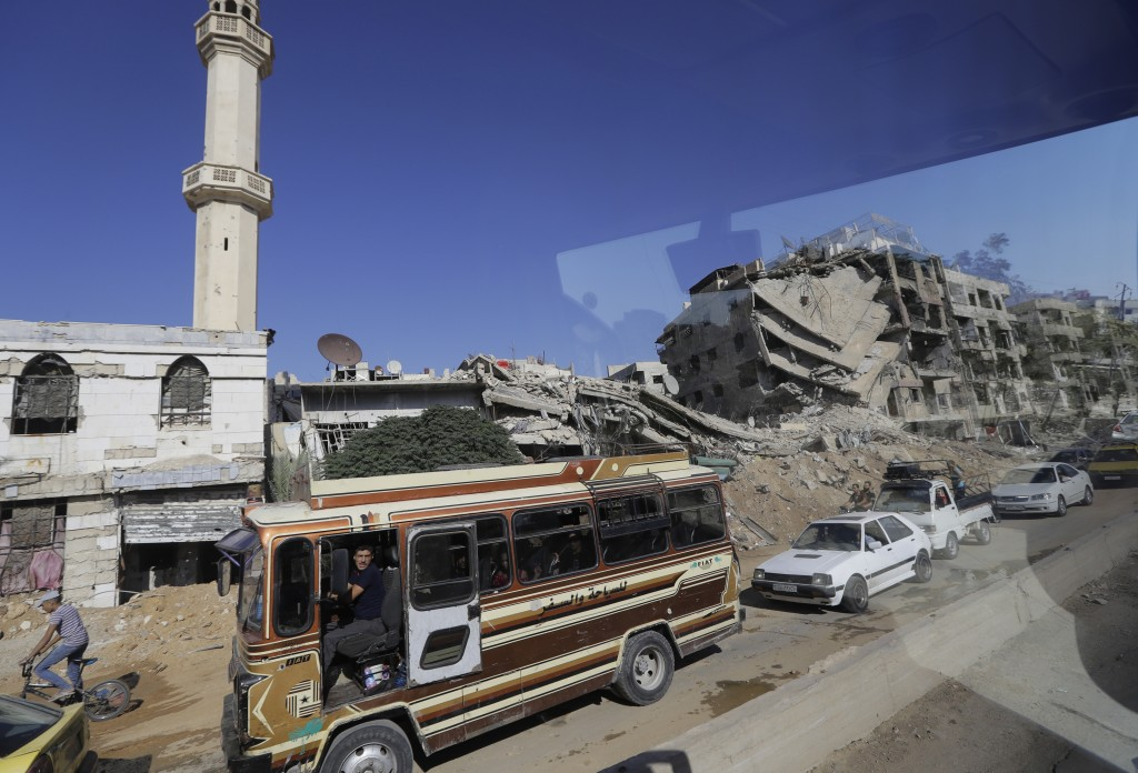 In a picture taken through a bus window, people drive their cars in Damascus, Syria, Monday, Aug. 13, 2018. Syrian government officials vowed Monday t...