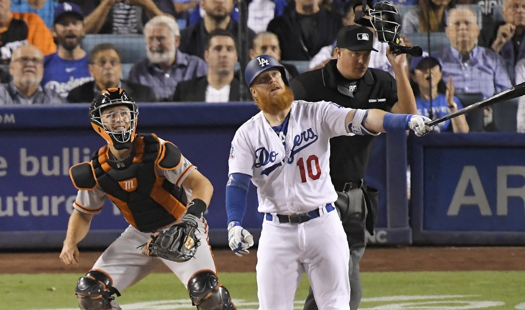 Los Angeles Dodgers' Justin Turner, center, hits a solo home run as San Francisco Giants catcher Buster Posey, left, and home plate umpire Cory Blaser...
