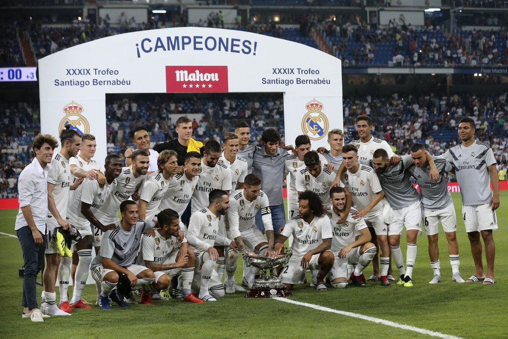 FILE - In this Saturday, Aug. 11, 2018 file photo, Real Madrid players pose with the trophy after winning the Santiago Bernabeu trophy soccer match be...