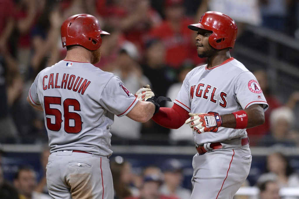 Los Angeles Angels' Justin Upton is greeted by Kole Calhoun after Upton hit a two-run home run during the 10th inning of a baseball game against the S...