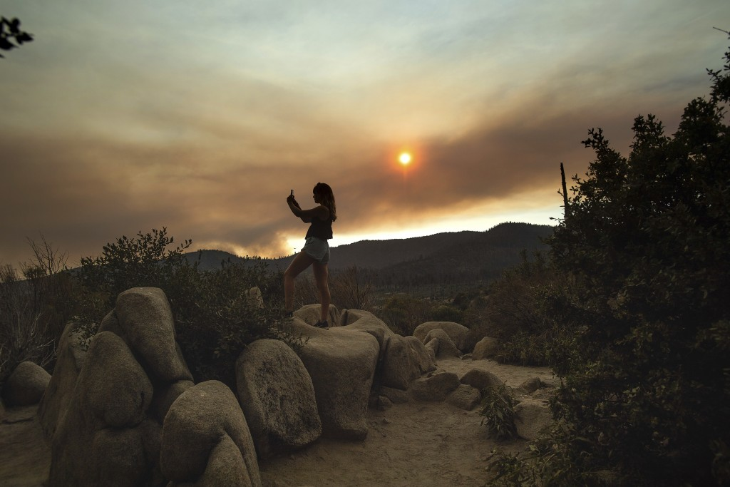 FILE - In this Tuesday, July 24, 2018, file photo, Mara Schumann photographs a plume of smoke from the Ferguson Fire in Yosemite National Park, Calif....