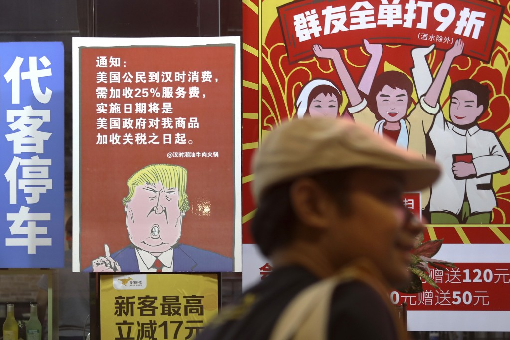 In this Monday, Aug. 13, 2018, photo, a man walks by a poster depicting a mural of U.S. President Donald Trump stating that all American costumers wil...