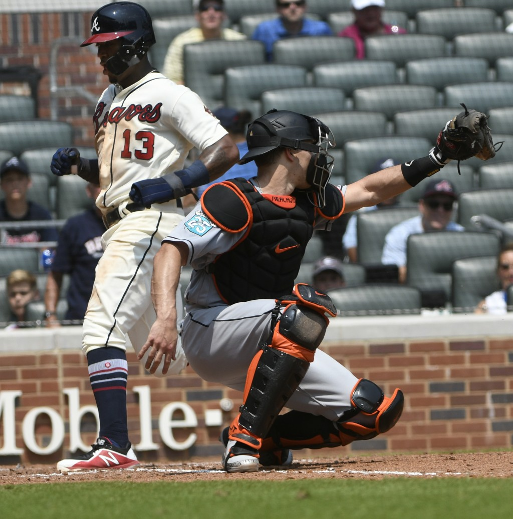Atlanta Braves' Ronald Acuna Jr. (13) scores on a sacrifice fly to left field by Freddie Freeman as Miami Marlins catcher J.T. Realmuto reaches for th...
