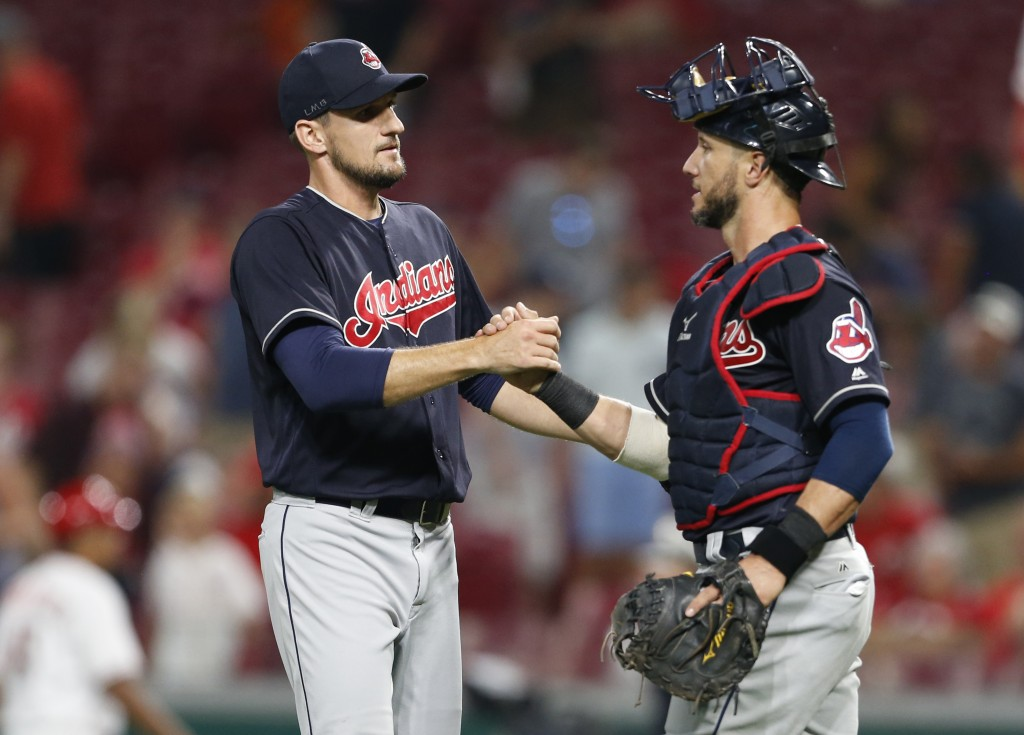 Cleveland Indians relief pitcher Dan Otero, left, and catcher Yan Gomes celebrate the team's 10-3 win over the Cincinnati Reds in a baseball game, Mon...