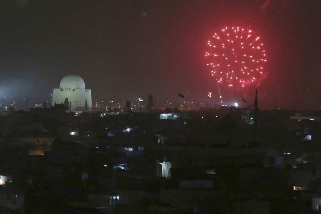Fireworks light the sky near the mausoleum of Mohammad Ali Jinnah, founder of Pakistan to celebrate the Independence Day in Karachi, Pakistan, Tuesday...