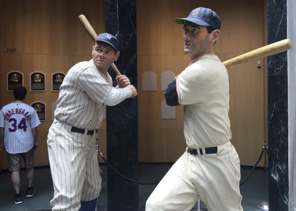 In this July 16, 2018 photo, baseball greats Babe Ruth, left, and Ted Williams are depicted at bat, in statues at the National Baseball Hall of Fame i...