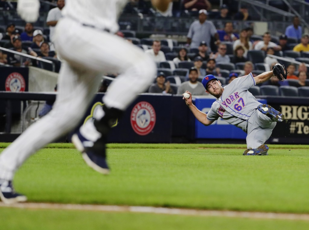 New York Mets starting pitcher Seth Lugo (67) attempts to throw out New York Yankees' Greg Bird during the eighth inning of a baseball game Monday, Au...