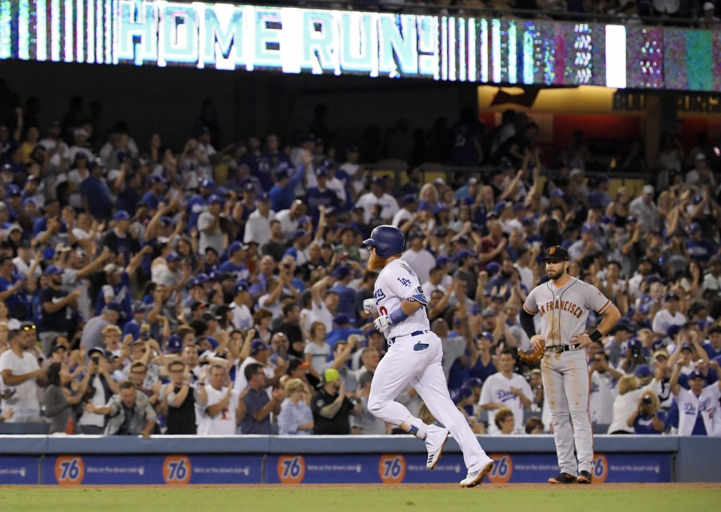Los Angeles Dodgers' Justin Turner, left, heads to third as he passes by San Francisco Giants third baseman Evan Longoria watches after Turner hit a s...
