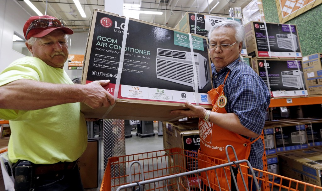 FILE - In this Aug. 1, 2017, file photo, store greeter Danny Olivar, right, lends a hand to a customer to heft an air conditioning unit from a rapidly...