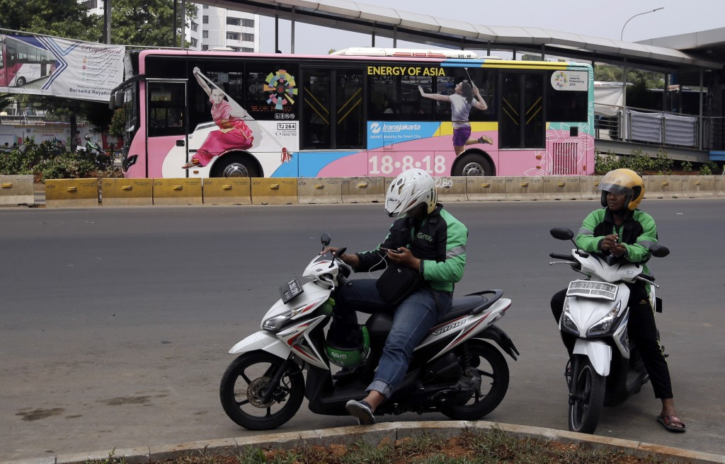 In this July 26, 2018, photo, motorcycle taxi drivers wait for customers as a bus with Asian Games promotional stickers drive past by at the main busi...