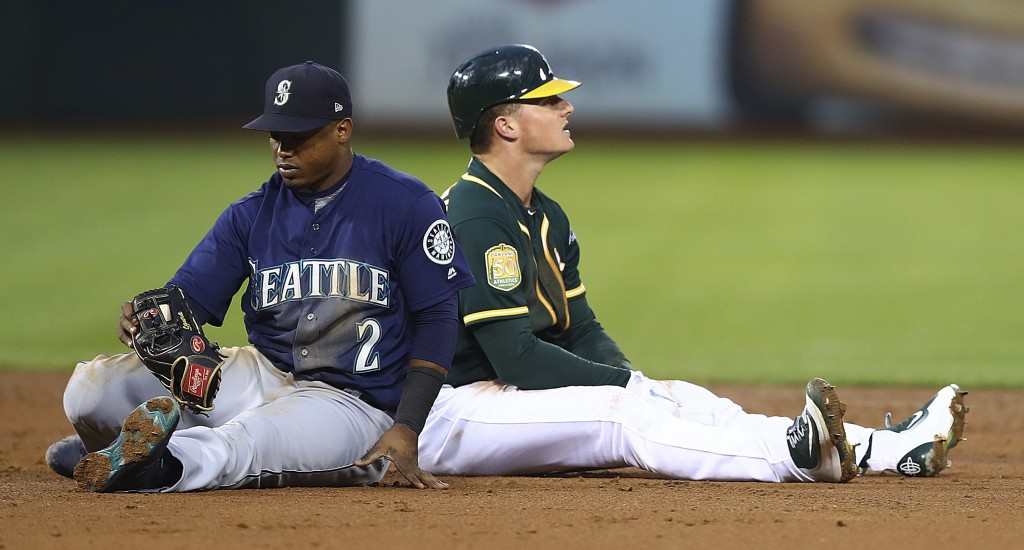 Seattle Mariners' Jean Segura (2) sits beside Oakland Athletics' Matt Chapman after Chapman beat Segura's tag into second base with a double in the th...