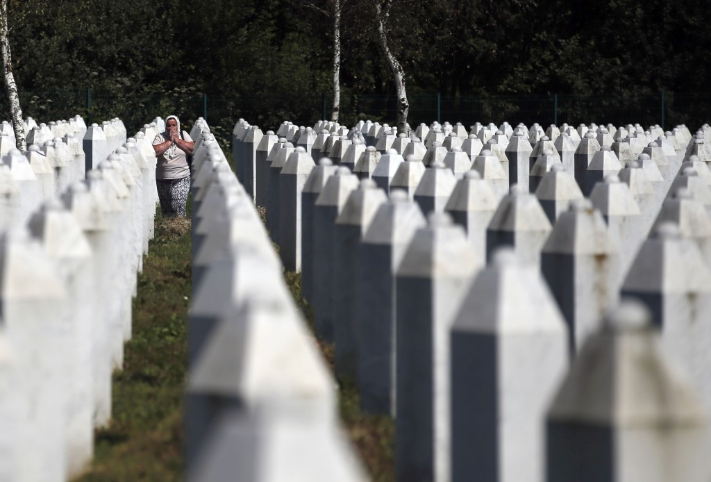 A Bosnian Muslim woman reacts as she walks among gravestones at the memorial centre of Potocari near Srebrenica, 150 kms north east of Sarajevo, Bosni...