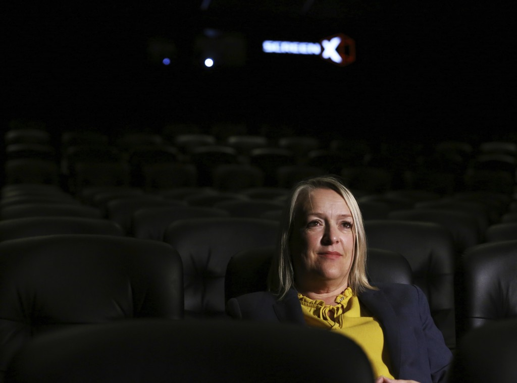 In this photo taken on Thursday, Aug. 9, 2018, Kelly Drew, an operations director at Cineworld, sits in the front row at Cineworld during a demonstrat...