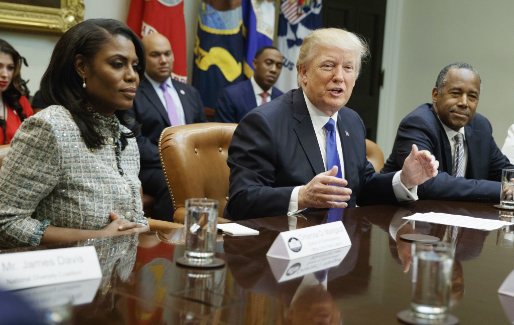 FILE - In this Feb. 1, 2017, file photo, President Donald Trump, center, is flanked by White House staffer Omarosa Manigault Newman, left, and  then-H...