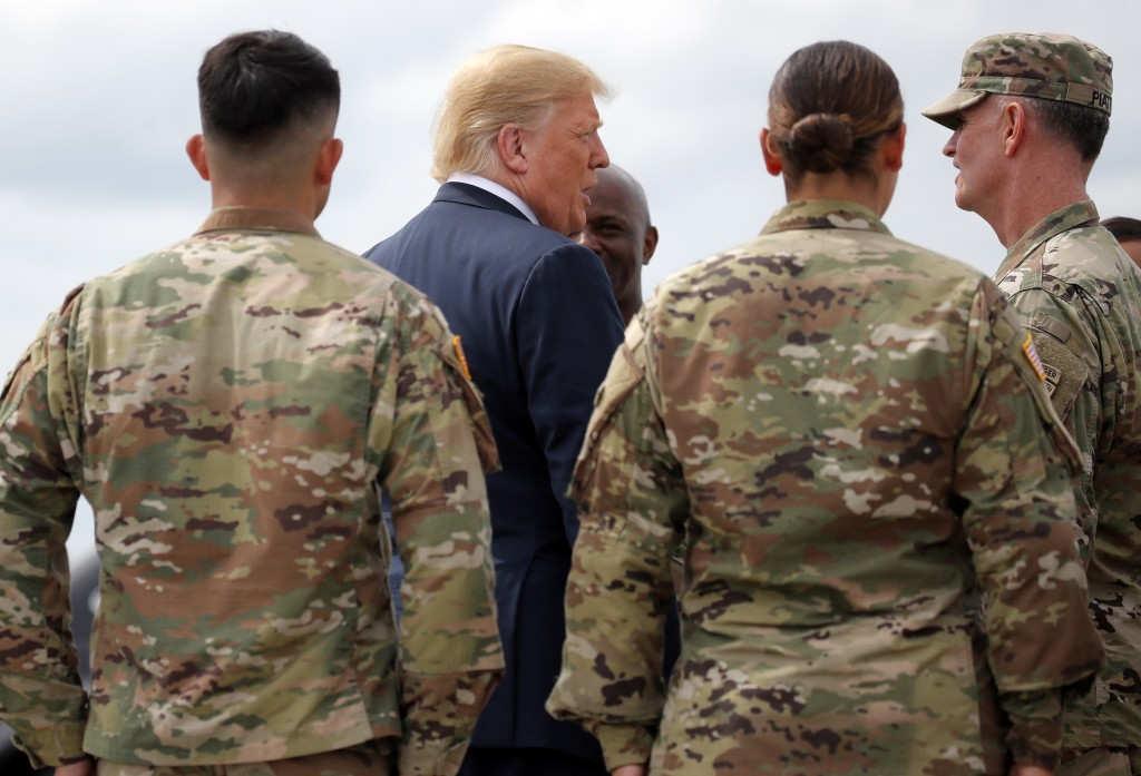 President Donald Trump greets member of the military as he arrives on Air Force One at Wheeler-Sack Army Air Field in Fort Drum, N.Y., Monday, Aug. 13...