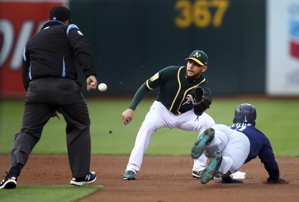 Oakland Athletics' Jed Lowrie waits for the ball to tag out Seattle Mariners' Jean Segura, right, in the first inning of a baseball game Monday, Aug. ...