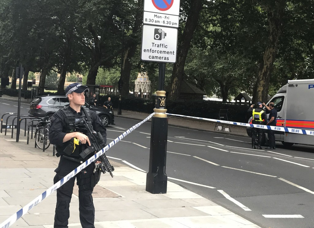 Police  patrol on Millbank, in central London, after a car crashed into security barriers outside the Houses of Parliament, in London,  Tuesday, Aug. ...